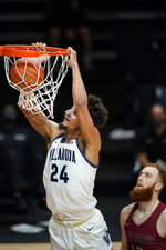 Villanova's Jeremiah Robinson-Earl, left, goes up for a dunk past Saint Joseph's Anthony Longpre during the first half of an NCAA college basketball game, Saturday, Dec. 19, 2020, in Villanova, Pa. (AP Photo/Matt Slocum)
