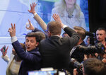 In this Sunday, April 21, 2019, photo, Ukrainian comedian and presidential candidate Volodymyr Zelenskiy, left, makes the victory sign after seeing the exit polls for the second round of presidential elections in Kiev, Ukraine. Ukrainians voted on Sunday in a presidential runoff as the nation's incumbent leader struggles to fend off a strong challenge by a comedian who denounces corruption and plays the role of president in a TV sitcom. (AP Photo/Vadim Ghirda)