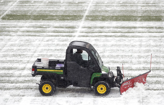 A grounds crew member clears snow from the playing surface in Folsom Field before the first half of an NCAA college football game between Utah and Colorado Saturday, Nov. 17, 2018, in Boulder, Colo. (AP Photo/David Zalubowski)