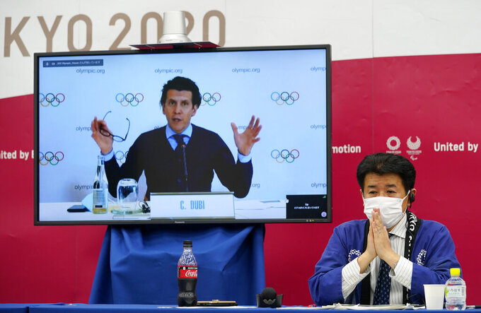 IOC's Olympic Games Executive Director Christophe Dubi appears on a screen to deliver an opening speech while Tokyo 2020 Games Delivery Officer Hidemasa Nakamura listens during a press briefing for the presentation of the Version Two of Tokyo 2020 Playbook in Tokyo, Japan, Wednesday April 28, 2021. The IOC and Tokyo 2020 organizers presented the second version of the playbook saying a third version will be unveiled in the coming weeks. (Franck Robichon / Pool via AP)