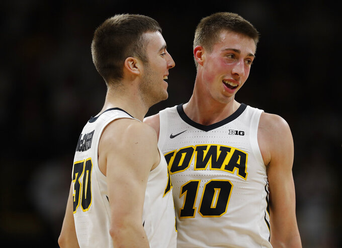 Iowa guard Connor McCaffery, left, congratulates Iowa guard Joe Wieskamp, right, after a three-point basket during the first half of an NCAA college basketball game against Illinois, Sunday, Jan. 20, 2019, in Iowa City. (AP Photo/Matthew Putney)