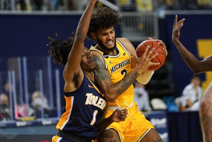 Michigan forward Isaiah Livers (2) drives on Toledo guard Jamere Hill (1) in the second half of an NCAA college basketball game in Ann Arbor, Mich., Wednesday, Dec. 9, 2020. (AP Photo/Paul Sancya)