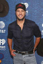FILE - In this May 5, 2018 file photo, Luke Bryan arrives at the iHeartCountry Festival at the Frank Erwin Center in Austin, Texas. Country singer and songwriter Bryan has hosted a free street concert to mark the opening of his new Tennessee restaurant that drew nearly 30,000 people to downtown Nashville. The Tennessean reports the concert on Monday, Sept. 10, 2018, marked the grand opening earlier that afternoon of Luke's 32 Bridge Food + Drink, a multi-story live entertainment complex. (Photo by Jack Plunkett/Invision/AP, File)