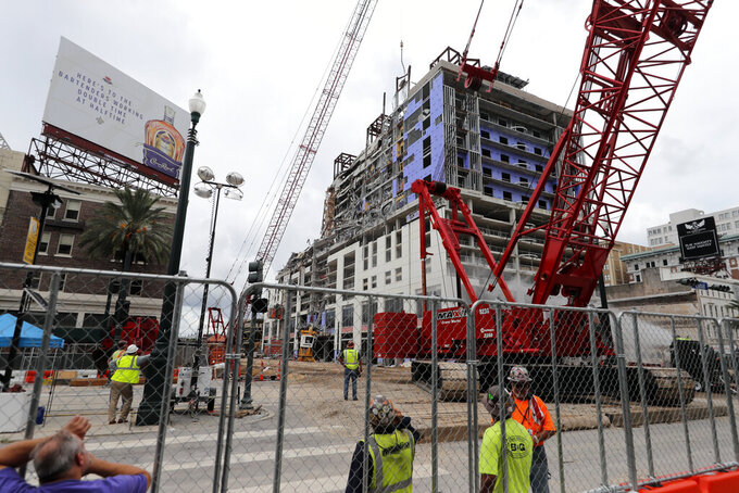 FILE - In this July 20, 2020, file photo, workers watch as a wrecking ball knocks debris loose from the Hard Rock Hotel building collapse site in New Orleans. New Orleans officials marked the return of two-way traffic to a major New Orleans thoroughfare Wednesday, April 28, 2021, more than 18 months after the partial collapse of a hotel under construction at the edge of the French Quarter killed three people and halted traffic and commerce on a section of historic Canal Street. (AP Photo/Gerald Herbert, File)