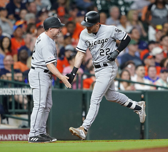 Chicago White Sox's Charlie Tilson (22) is congratulated by third base coach Nick Capra after hitting a grand slam against the Houston Astros during the sixth inning of a baseball game Wednesday, May 22, 2019, in Houston. (AP Photo/David J. Phillip)