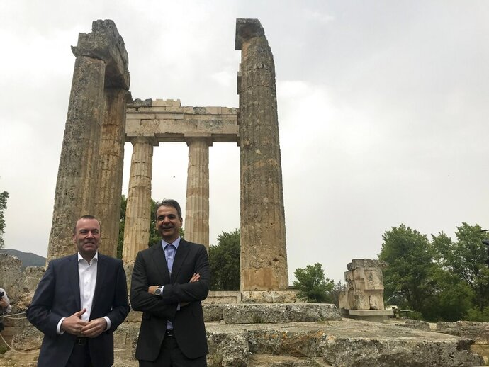 European People's Party candidate Manfred Weber, left, and the leader of Greece's conservative New Democracy party Kyriakos Mitsotakis visit an ancient temple at Nemea about 117 kilometers (73 miles) west of Athens on Tuesday, April 23, 2019. Weber is in Greece for the official launch of his campaign for the May 23-26 European Parliament elections. (AP Photo/Derek Gatopoulos)