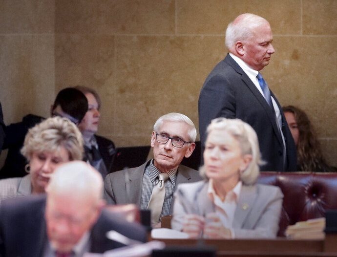 Wisconsin Gov. Tony Evers, seated at center, listens to a Senate debate regarding his pick to head the Department of Agriculture, Trade, and Consumer Protection during a session at the Wisconsin State Capitol in Madison, Wis. Tuesday, Nov. 5, 2019. Walking behind during the proceedings is Senate Majority Leader Scott Fitzgerald, R-Juneau. (John Hart/Wisconsin State Journal via AP)