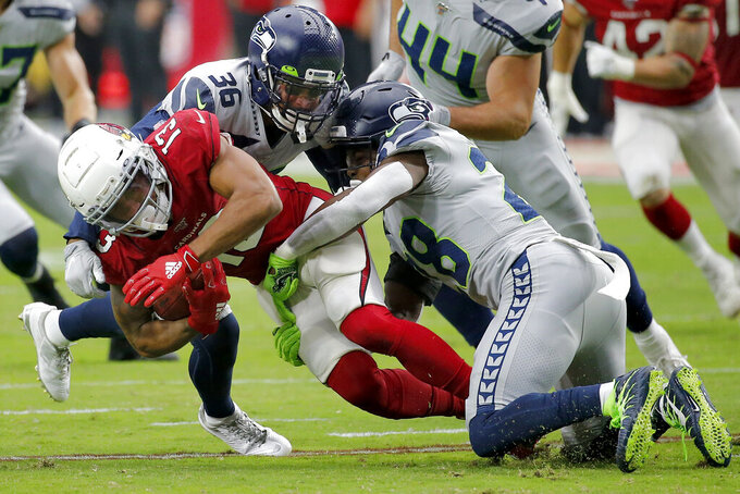 Arizona Cardinals wide receiver Christian Kirk (13) is tackled by Seattle Seahawks cornerback Akeem King (36) and cornerback Ugo Amadi (28) during the second half of an NFL football game, Sunday, Sept. 29, 2019, in Glendale, Ariz. (AP Photo/Rick Scuteri)