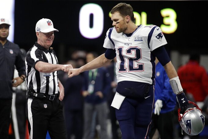 Referee John Parry, left, bumps fists with New England Patriots' Tom Brady before the NFL Super Bowl 53 football game between the Patriots and the Los Angeles Rams, Sunday, Feb. 3, 2019, in Atlanta. (AP Photo/Patrick Semansky)
