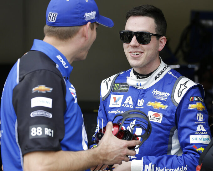 Alex Bowman, right, talks with one of his crew members during a NASCAR auto racing practice at Daytona International Speedway, Saturday, Feb. 16, 2019, in Daytona Beach, Fla. (AP Photo/Terry Renna)