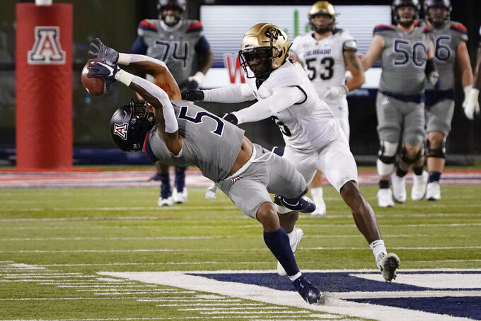 Arizona wide receiver Brian Casteel, left, makes a catch in front of Colorado safety Mark Perry in the first half during an NCAA college football game, Saturday, Dec. 5, 2020, in Tucson, Ariz. (AP Photo/Rick Scuteri)