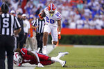 Florida running back Malik Davis (20) hurdles Florida Atlantic linebacker Antarrius Moultrie (1) for extra yardage during the first half of an NCAA college football game Saturday, Sept. 4, 2021, in Gainesville, Fla. (AP Photo/John Raoux)