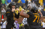 Missouri quarterback Drew Lock, left, celebrates with teammate Kevin Pendleton after Lock scored a touchdown during the first half of an NCAA college football game against Arkansas Friday, Nov. 23, 2018, in Columbia, Mo. (AP Photo/L.G. Patterson)