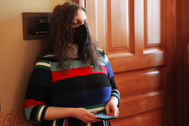 In this photo from Friday, Jan. 15, 2021, Rachel Sweet, a lobbyist for Planned Parenthood Great Plains, watches a legislative committee hearing on a proposed anti-abortion amendment to the state constitution in a hallway just outside the meeting room at the Statehouse in Topeka, Kan. The proposed amendment would overturn a 2019 Kansas Supreme Court decision declaring access to abortion a