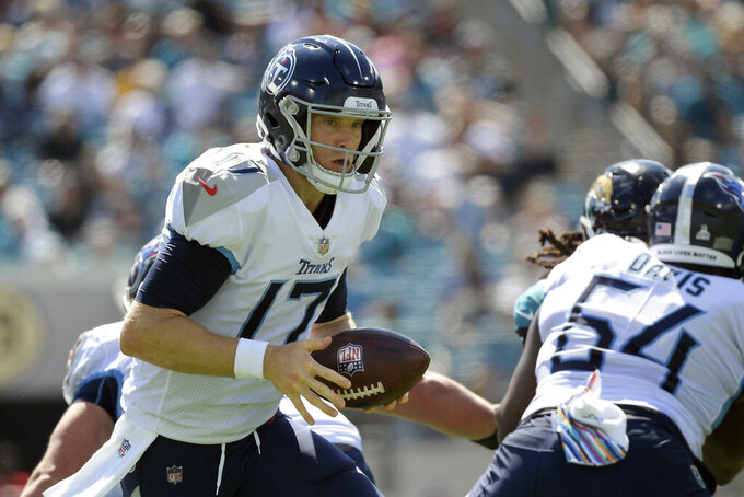 Tennessee Titans quarterback Ryan Tannehill (17) hands off the ball during the first half of an NFL football game against the Tennessee Titans, Sunday, Oct. 10, 2021, in Jacksonville, Fla. (AP Photo/Phelan M. Ebenhack)