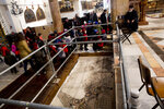 In this Thursday, Dec. 6, 2018 photo, visitors walk by a renovated part of a mosaic inside the Church of the Nativity, built atop the site where Christians believe Jesus Christ was born, in the West Bank City of Bethlehem. City officials are optimistic that the renovated church will help add to a recent tourism boom and give a boost to the shrinking local Christian population. (AP Photo/Majdi Mohammed)