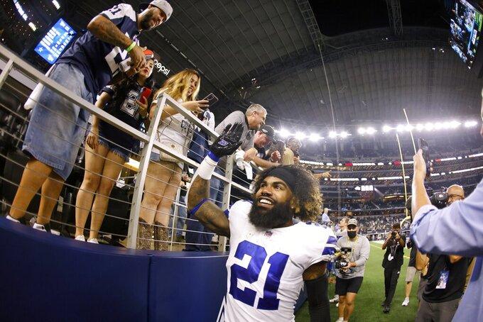 Dallas Cowboys running back Ezekiel Elliott (21) celebrates with fans after an NFL football game against the Philadelphia Eagles in Arlington, Texas, Monday, Sept. 27, 2021. (AP Photo/Ron Jenkins)