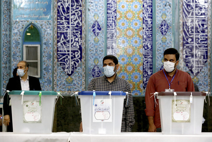 Iranian election officials wait for voters during the presidential election at a polling station in Tehran, Iran, Friday, June 18, 2021. Iran began voting Friday in a presidential election tipped in the favor of a hard-line protege of Supreme Leader Ayatollah Ali Khamenei, fueling public apathy and sparking calls for a boycott in the Islamic Republic. (AP Photo/Ebrahim Noroozi)