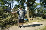 Eric Fish takes a break from hauling downed branches in front of his home, Friday, Aug. 14, 2020, in Cedar Rapids, Iowa. The storm that struck Monday morning left  tens of thousands of Iowans without power as of Friday morning. (AP Photo/Charlie Neibergall)