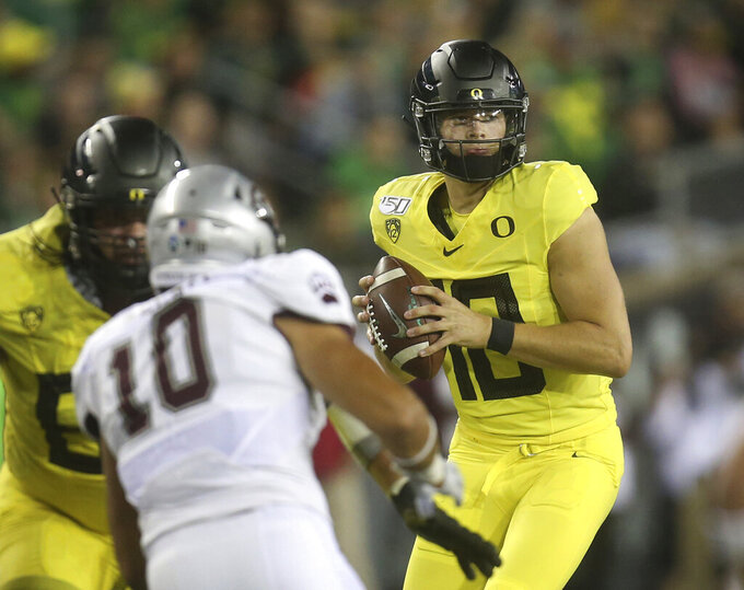 Oregon's Justin Herbert, right, looks down field against Montana during the third quarter of an NCAA college football game Saturday, Sept. 14, 2019, in Eugene, Ore. (AP Photo/Chris Pietsch)