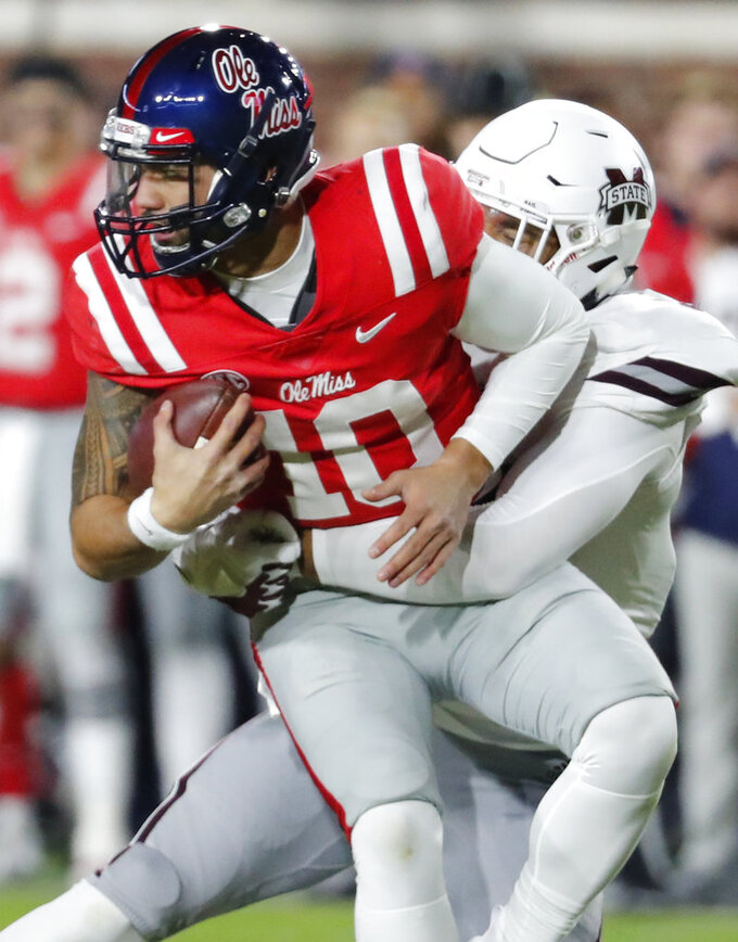 Mississippi quarterback Jordan Ta'amu (10) is sacked by Mississippi State defensive end Montez Sweat (9) during the first half of an NCAA college football game in Oxford, Miss., Thursday, Nov. 22, 2018. (AP Photo/Rogelio V. Solis)