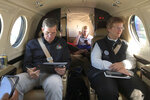 North Carolina Gov. Roy Cooper, left, makes notes on a report as FEMA Coordinating Officer Libby Turner looks out the window of their plane on the way to the coast, Friday, Sept. 6, 2019, over N.C. (AP Photo/Allen Breed, Pool)