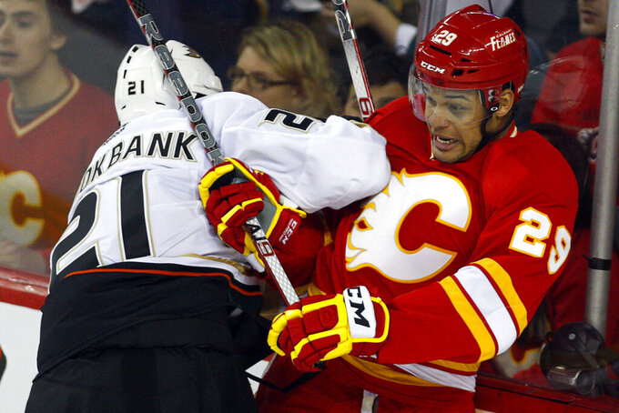 "FILE - In this April 7, 2012, file photo, Anaheim Ducks' Sheldon Brookbank, left, checks Calgary Flames' Akim Aliu, a Nigerian-born Canadian, during third period NHL hockey action in Calgary, Alberta. Calgary Flames general manager Brad Treliving said the team is looking into an accusation that head coach Bill Peters directed racial slurs toward a Nigerian-born hockey player a decade ago in the minor leagues, then arranged for the player's demotion when he complained. Akim Aliu tweeted Monday, Nov. 25, 2019, that Peters ""dropped the N bomb several times towards me in the dressing room in my rookie year because he didn't like my choice of music."" (AP Photo/The Canadian Press, Jeff McIntosh, File)"