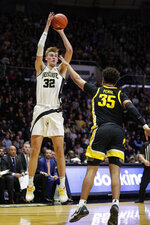 File-This Feb. 5, 2020, file photo shows Purdue center Matt Haarms (32) shooting over Iowa forward Cordell Pemsl (35) during the second half of an NCAA college basketball game in West Lafayette, Ind. This 7-foot-3 graduate student transferred to BYU after averaging 7.5 points, 4.4 rebounds, and 2.1 blocks over 102 games at Purdue.  (AP Photo/Michael Conroy, File)