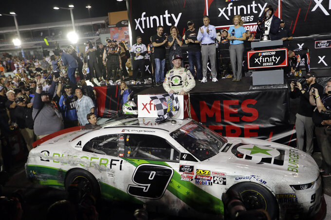 Tyler Reddick stands with his car after winning the NASCAR Xfinity Series championship auto race at the Homestead-Miami Speedway, Saturday, Nov. 17, 2018, in Homestead, Fla. (AP Photo/Lynne Sladky)
