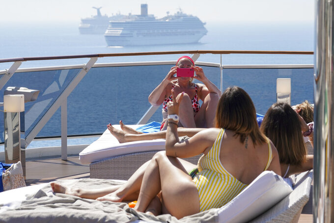 Passengers take selfies on a deck of the MSC Grandiosa cruise ship in Civitavecchia, near Rome, Wednesday, March 31, 2021. MSC Grandiosa, the world's only cruise ship to be operating at the moment, left from Genoa on March 30 and stopped in Civitavecchia near Rome to pick up more passengers and then sail toward Naples, Cagliari, and Malta to be back in Genoa on April 6. For most of the winter, the MSC Grandiosa has been a lonely flag-bearer of the global cruise industry stalled by the pandemic, plying the Mediterranean Sea with seven-night cruises along Italy's western coast, its major islands and a stop in Malta. (AP Photo/Andrew Medichini)