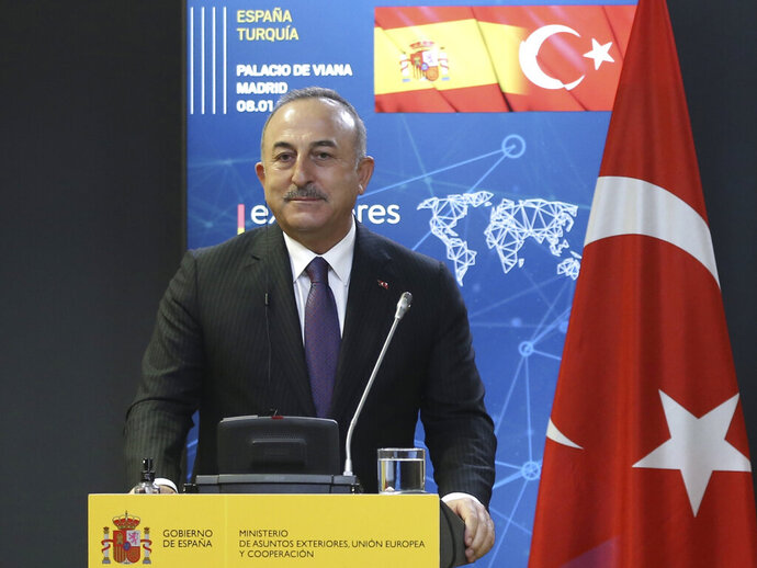 Turkish Foreign Minister Mevlut Cavusoglu speaks at a news conference in Madrid, Spain, Friday, Jan. 8, 2021. Turkey on Monday, Jan. 11 invited Greece to resume talks designed to reduce tensions between the neighbors, following this summer's dispute over maritime borders and energy rights in the eastern Mediterranean. Cavusoglu also extended an invitation to Greek Foreign Minister Nikos Dendias, for a meeting to discuss their troubled relations.(Turkish Foreign Ministry via AP, Pool)
