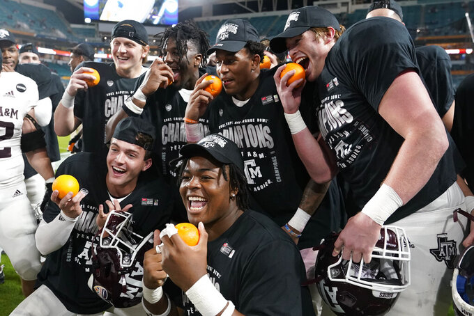 Texas A&M players pose for photos at the end of the Orange Bowl NCAA college football game, Saturday, Jan. 2, 2021, in Miami Gardens, Fla. Texas A&M defeated North Carolina 41-27. (AP Photo/Lynne Sladky)