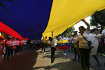 Opposition members carry a Venezuelan flag during a protest against Venezuela's President Nicolas Maduro in Urena, Venezuela, Tuesday, Feb. 12, 2019. during a protest against his government in Urena, Venezuela, Tuesday, Feb. 12, 2019. Nearly three weeks after the Trump administration backed an all-out effort to force out President Nicolas Maduro, the embattled socialist leader is holding strong and defying predictions of an imminent demise. (AP Photo/Fernando Llano)