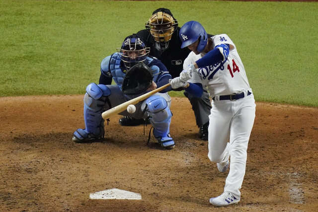 Los Angeles Dodgers' Enrique Hernandez hits a RBI-single against the Tampa Bay Rays during the fifth inning in Game 1 of the baseball World Series Tuesday, Oct. 20, 2020, in Arlington, Texas. (AP Photo/Sue Ogrocki)