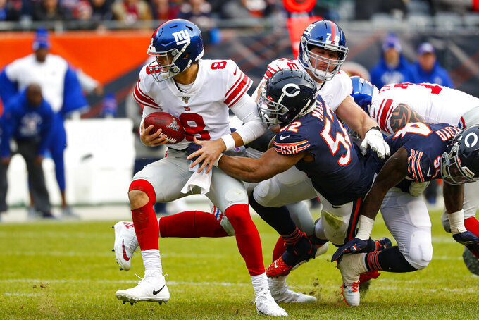 New York Giants quarterback Daniel Jones (8) escapes the grasp of Chicago Bears outside linebacker Khalil Mack (52) during the second half of an NFL football game in Chicago, Sunday, Nov. 24, 2019. (AP Photo/Paul Sancya)