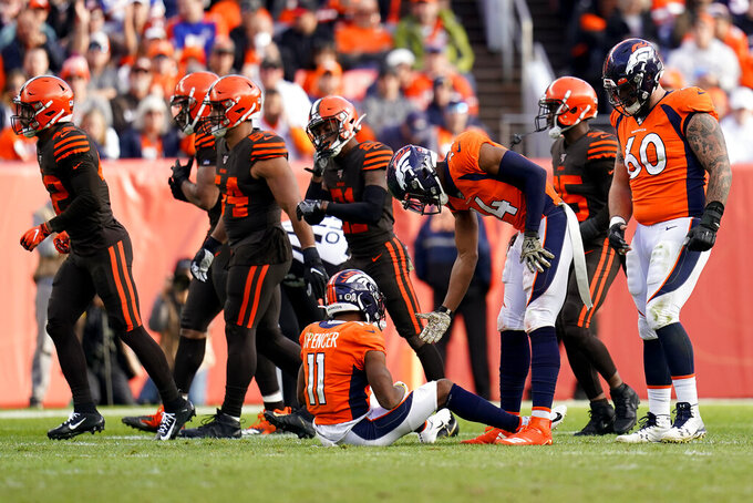 Denver Broncos wide receiver Diontae Spencer (11) is helped up by teammate Courtland Sutton (14) after fumbling the football against the Cleveland Browns during the first half of NFL football game, Sunday, Nov. 3, 2019, in Denver. The Browns recovered the ball. (AP Photo/Jack Dempsey)