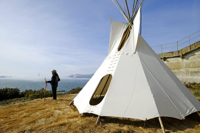 In this photo taken Tuesday, Nov. 12, 2019, Eloy Martinez, who took part in the Native American occupation of Alcatraz 50 years earlier, stands by a teepee on the island and looks out toward the bay and Golden Gate Bridge in San Francisco. The week of Nov. 18, 2019, marks 50 years since the beginning of a months-long Native American occupation at Alcatraz Island in the San Francisco Bay. (AP Photo/Eric Risberg)