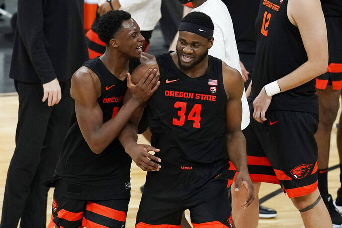 Oregon State's Warith Alatishe, left, and Rodrigue Andela (34) celebrate after defeating Oregon in an NCAA college basketball game in the semifinal round of the Pac-12 men's tournament Friday, March 12, 2021, in Las Vegas. (AP Photo/John Locher)