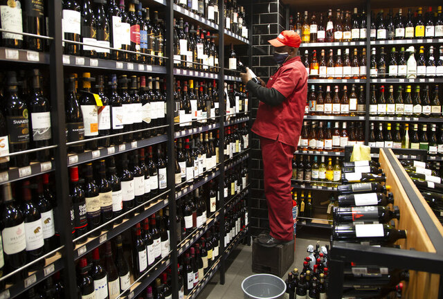 A man stocks shelves with bottles of wine at a Johannesburg liquor store in Johannesburg Monday, Aug. 17, 2020, as the country will lift its coronavirus-linked ban on the sale of alcohol and tobacco products on Tuesday. The purchase of alcohol and cigarettes was banned when the country went into a strict nationwide lockdown on 27 March to stem the spread of coronavirus. (AP Photo/Denis Farrell)
