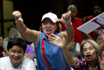 Frustrated supporters of the Pheu Thai party cheer as election results are broadcast on a television in Bangkok, Thailand, Sunday, March 24, 2019. Figures from Thailand's Election Commission show a military-backed party has taken the lead in the country's first election since a 2014 coup. (AP Photo/Gemunu Amarasinghe)