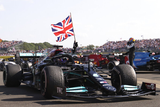 Mercedes driver Lewis Hamilton of Britain celebrates after winning the British Formula One Grand Prix, at the Silverstone circuit, in Silverstone, England, Sunday, July 18, 2021. (Lars Baron/Pool photo via AP)