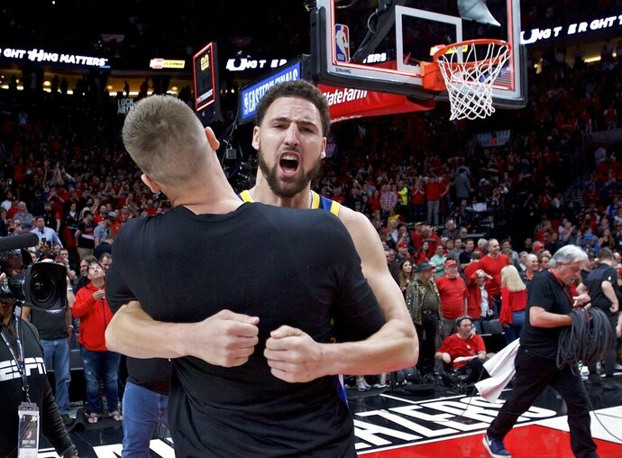 Golden State Warriors guard Klay Thompson hugs forward Jonas Jerebko at the end of Game 4 of the NBA basketball playoffs Western Conference finals against the Portland Trail Blazers Monday, May 20, 2019, in Portland, Ore. The Warriors won 119-117 in overtime. (AP Photo/Craig Mitchelldyer)