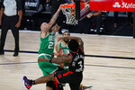 Boston Celtics center Daniel Theis (27) gets a dunk over Toronto Raptors forward OG Anunoby (3) during the second half of an NBA conference semifinal playoff basketball game Wednesday, Sept. 9, 2020, in Lake Buena Vista, Fla. (AP Photo/Mark J. Terrill)
