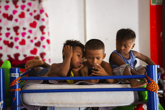 Haitian migrant children watch programing at a shelter, Friday, Sept. 17, 2021, in Ciudad Acuña, Mexico. Haitians crossed the Rio Grande freely and in a steady stream, going back and forth between the U.S. and Mexico through knee-deep water with some parents carrying small children on their shoulders. Unable to buy supplies in the U.S., they returned briefly to Mexico for food and cardboard to settle, temporarily at least, under or near the bridge in Del Rio, a city of 35,000 that has been severely strained by migrant flows in recent months. (Marie D. De Jesús/Houston Chronicle via AP)