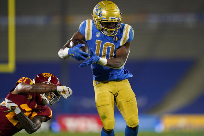 UCLA running back Demetric Felton (10) runs to the end zone for a touchdown past Southern California linebacker Palaie Gaoteote IV during the second quarter of an NCAA college football game Saturday, Dec 12, 2020, in Pasadena, Calif. (AP Photo/Ashley Landis)
