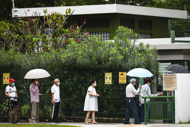 Voters wear face masks and observe social distancing as they line up to enter the Alexandra Primary School polling center in Singapore Friday, July 10, 2020. Wearing masks and plastic gloves, Singaporeans began voting in a general election that is expected to return Prime Minister Lee Hsien Loong's long-governing party to power. (AP Photo)