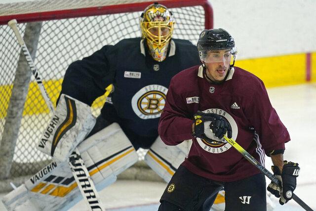 Boston Bruins' Brad Marchand looks for a pass while goaltender Tuukka Rask minds the net at NHL hockey training camp, Monday, Jan. 4, 2021, in Boston. (AP Photo/Elise Amendola)