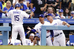 Los Angeles Dodgers' Austin Barnes, left, is congratulated by manager Dave Roberts, second from right, and bench coach Bob Geren, right, after hitting a solo home run during the second inning of a baseball game against the Colorado Rockies Saturday, July 24, 2021, in Los Angeles. (AP Photo/Mark J. Terrill)
