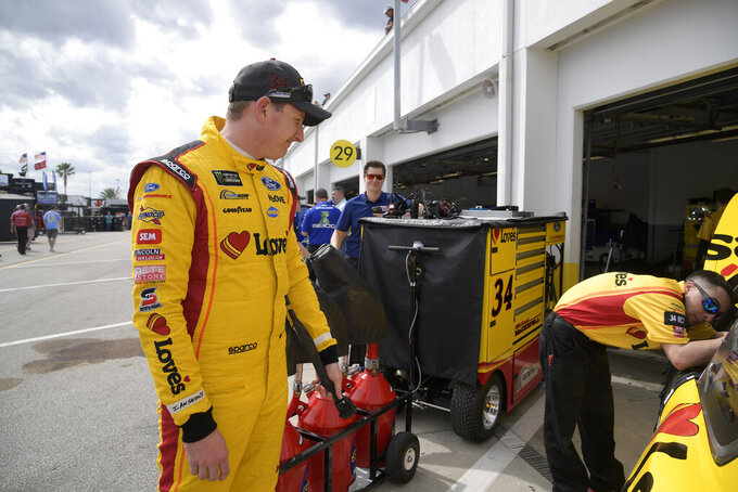 Driver Michael McDowell, left, stands outside his car in the garage area during a practice session for the NASCAR Daytona 500 auto race at Daytona International Speedway Saturday, Feb. 16, 2019, in Daytona Beach, Fla. (AP Photo/Phelan M. Ebenhack)