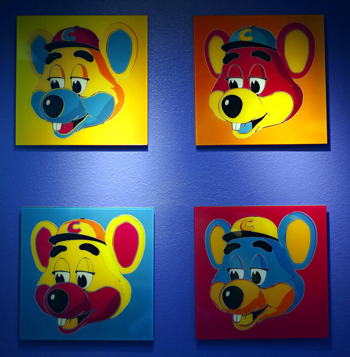 """FILE - This Jan. 16, 2014 file photo shows paintings hanging  on a wall at Chuck E. Cheese's in Dallas. Chuck E. Cheese pizzeria, that Mecca of fun for children but the bane of many parents, is filing for bankruptcy protection. CEC Entertainment Inc. said Thursday, Jan. 25, 2020,  it was filing for voluntary protection under Chapter 11 """"in order to overcome the financial strain resulting from prolonged, COVID-19 related venue closures.""""  (G.J. McCarthy/The Dallas Morning News via AP)"""